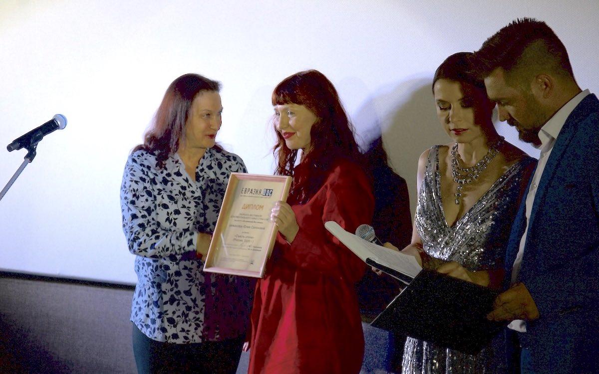 Наталия Гугуева вручает Диплом «Евразия.DOC» автору фильма «Съесть слона» — Юлии Сапоновой. Справа — ведущие